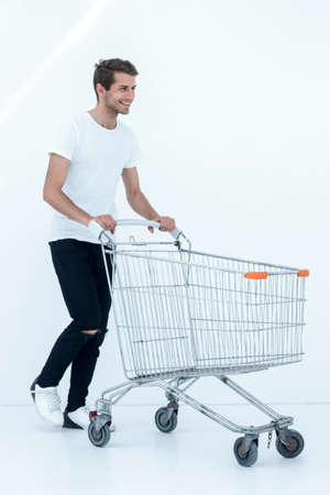 smiling man pushing shopping cart. Banco de Imagens