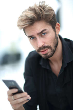 A stylish bearded male sits and uses a smartphone.