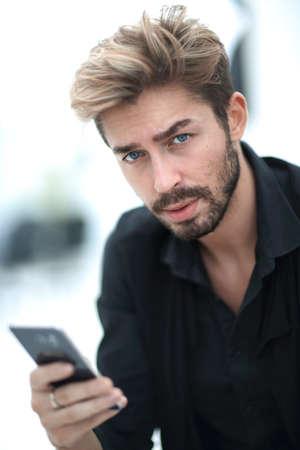 A stylish bearded male sits and uses a smartphone.