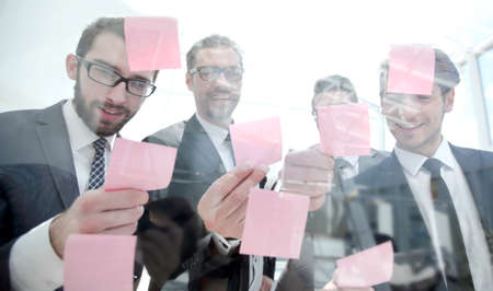 close up.successful employees reading sticky notes on glas Фото со стока