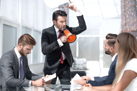 angry boss shouting at employees through a megaphone