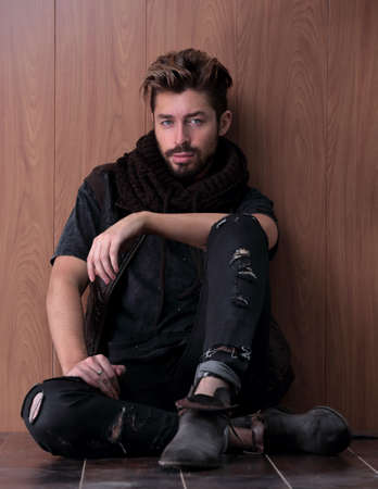 Handsome mature man sitting by the brick wall. Mens fashion.