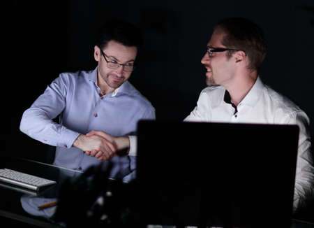 handshake colleagues sitting at the Desk