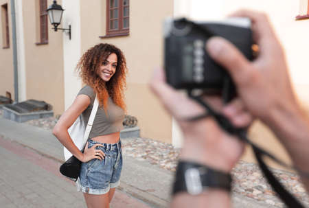 Beautiful brown curly hair  woman posing in city Banco de Imagens