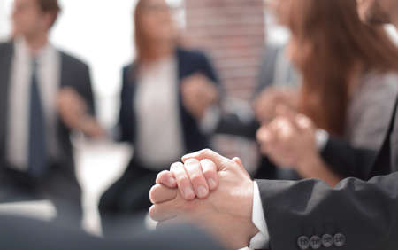 Business group in a circle holding hands indoors