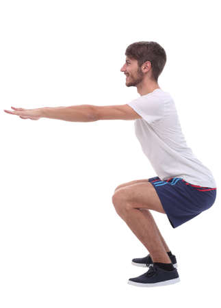 Full length.active male performs squats with straight arms.
