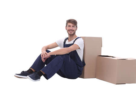 in full growth. smiling man sitting near cardboard boxes