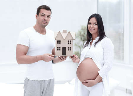 husband showing his pregnant wife a layout of their future home.