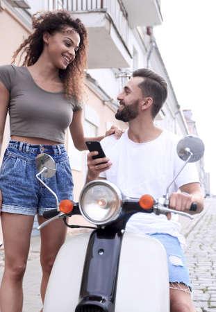 Joven pareja feliz montando scooter juntos sonriendo Foto de archivo