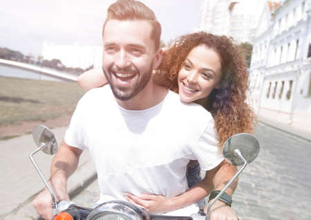 Happy cheerful couple riding vintage scooter outdoors.