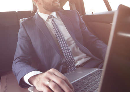 Confident businessman sitting in car