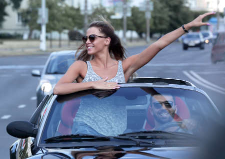 happy young woman standing in convertible car Zdjęcie Seryjne