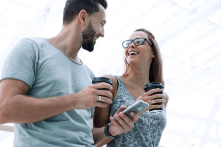 young couple drinks coffee and uses a smartphone on the street o