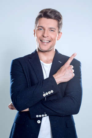 Attractive young man in suit pointing up with his finger isolate