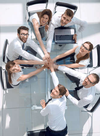 top view of young business people putting their hands together