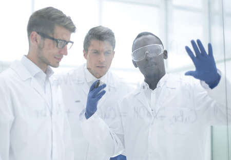 group of scientists consider the records on a glass Board