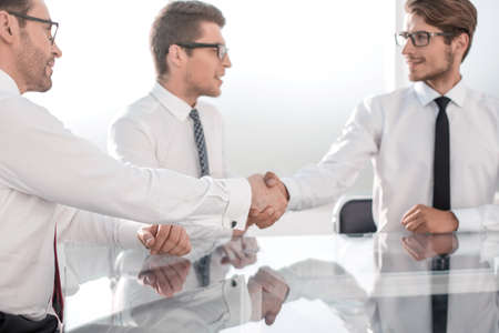 business partners shake hands while sitting at the table.