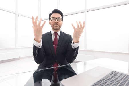 serious businessman explains something sitting at his Desk Stock Photo