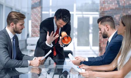 businessman talking to the business team through a megaphone