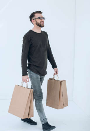 Portrait of a man with a full paper bag on a gray