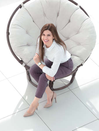 top view.young woman sitting in soft round chair Standard-Bild