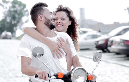 Happy young couple riding a scooter in the city on a sunny day Stock Photo