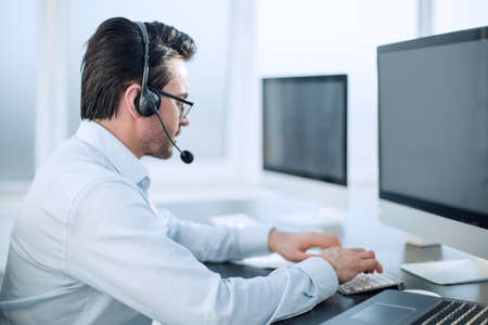 close up.businessman with a headset works in a modern office 版權商用圖片