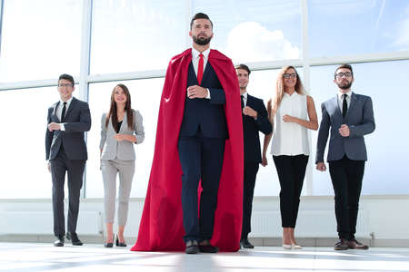businessman-superhero and business team standing in the office.
