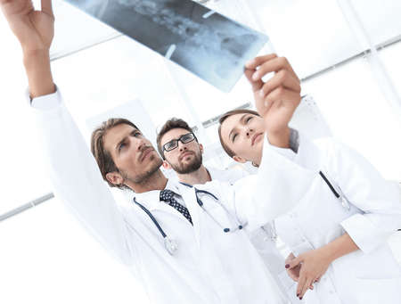 Portrait of happy surgeons holding x-ray report