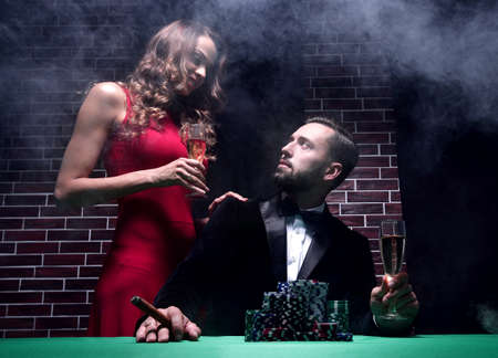 Couple in the casino playing poker on green felt