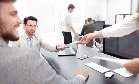 assistant giving documents to the businessman