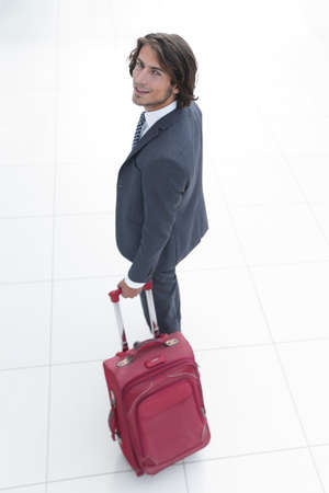 top view and rear.businessman with travel suitcase goes out. Reklamní fotografie