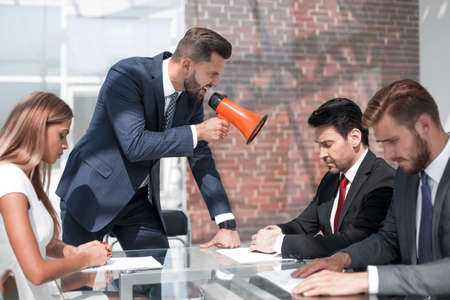 businessman yelling at his colleagues through a megaphone