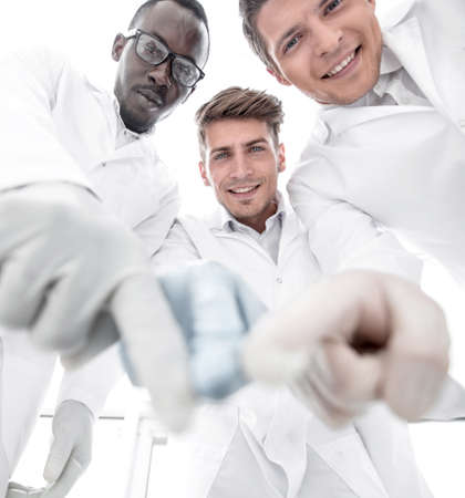 group of scientists pointing to the laboratory table