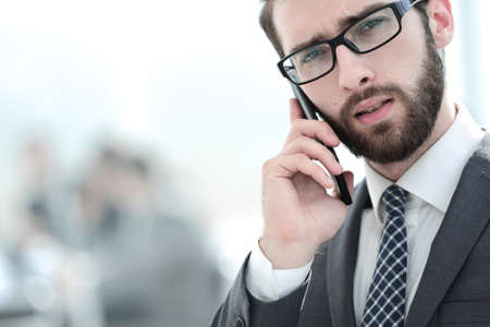 businessman talking on smartphone on office background