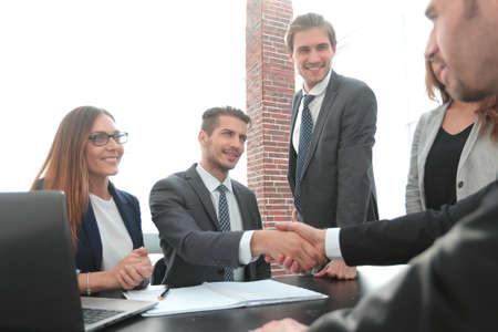 un apretón de manos después de una reunión de negocios en la oficina