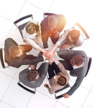 top view.a group of employees with their hands folded together Фото со стока