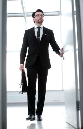 businessman with a leather briefcase entering his clients office.