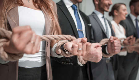 Hands of business people connected by ropes