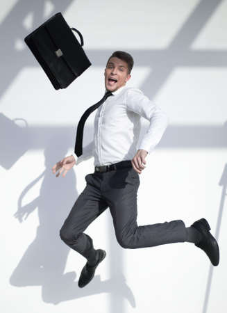 business man jumping in the air with a large smile on his face Stok Fotoğraf