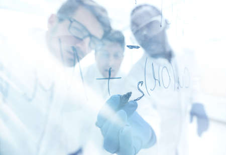 close up.a group of scientists recording the formula on a glass