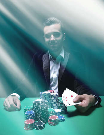 Happy poker player winning and holding a pair of aces 写真素材