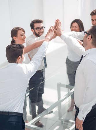 successful business teams make a high five over their Desk Banco de Imagens