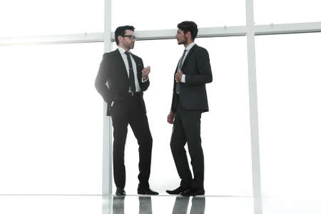 two businessmen standing near a large office window