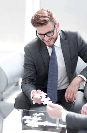 smiling businessman helping the partner to complete the puzzle Standard-Bild