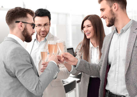 business team raises glasses of champagne in the office