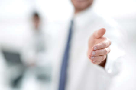 blurred image. business man holding out his hand for a handshake.business background