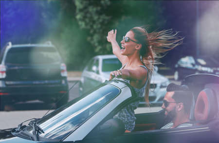 happy young woman enjoying a ride in a convertible car