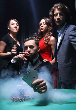 Rich handsome man smoking cigar and playing in the casino