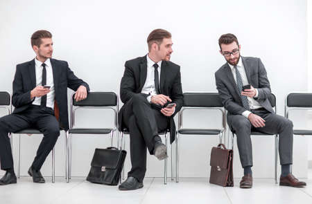 employees with smartphones sitting in the office hallway